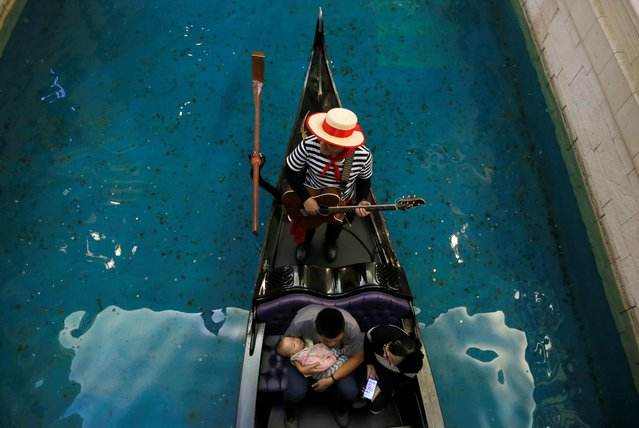 A boy sleeps as the family take a gondola ride inside the shopping mall of the Venetian Macao hotel and casino in Macau, China December 19, 2019, on the eve of the 20th anniversary of the former Portuguese colony's return to China. (Photo by Jason Lee/Reuters)