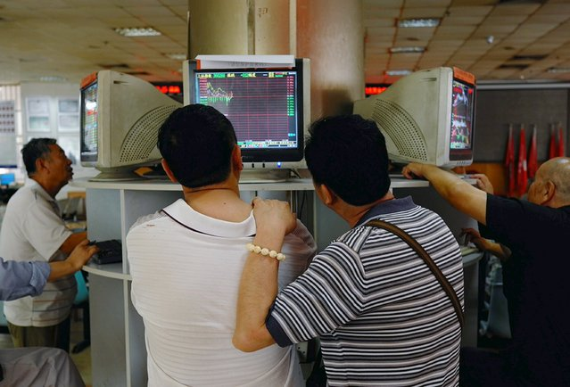Investors look at computer screens showing stock information at a brokerage house in Beijing, China, July 29, 2015. China stocks ended a three-day slide and recorded its biggest daily gain in 1-1/2 weeks on Wednesday, after Beijing reiterated its determination to stabilize its volatile equity markets. (Photo by Reuters/Stringer)