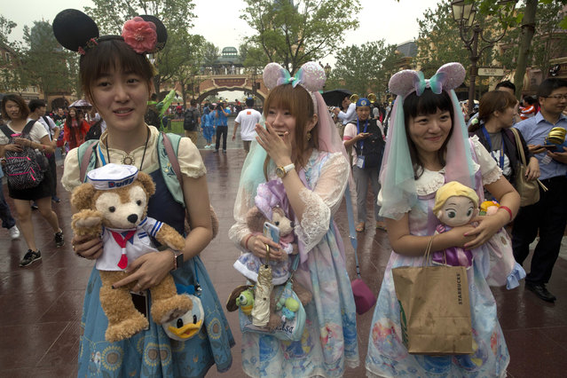 Visitors dress up as they attend the opening day of the Disney Resort in Shanghai, China, Thursday, June 16, 2016. (Photo by Ng Han Guan/AP Photo)