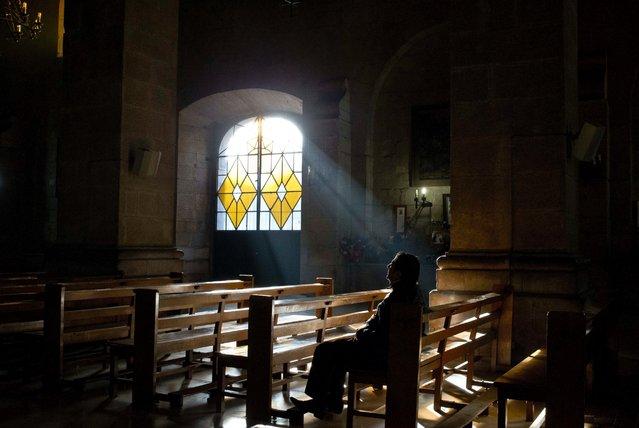 A man prays inside the Santo Domingo Catholic church in Santiago, Chile, Friday, June 17, 2016. (Photo by Esteban Felix/AP Photo)