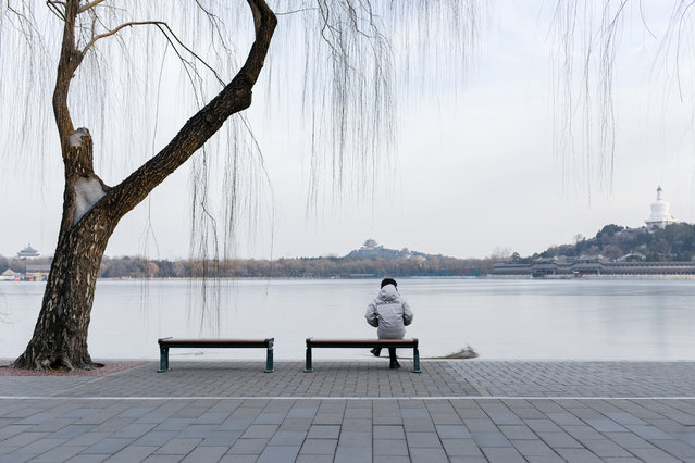 A woman rests on a bench at a park in Beijing on January 2, 2020. (Photo by Wang Zhao/AFP Photo)
