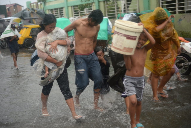 Residents brave strong winds and rain as they evacuate from their homes at an informal settlers' area as Typhoon Rammasun barrels across Manila on July 16, 2014. Typhoon Rammasun shut down the Philippine capital on July 16 as authorities said the first major storm of the country's brutal rainy season claimed at least one life and forced hundreds of thousands to evacuate. (Photo by Ted Aljibe/AFP Photo)
