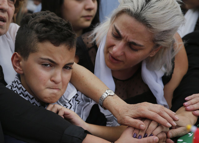 Omar, left, and his mother Lara, the son and the wife of of Alaa Abu Fakher, who was killed by a Lebanese soldier in Tuesday night protests south of Beirut, attend his funeral, in Choueifat neighborhood, Lebanon, Thursday, November 14, 2019. For nearly a month, the popular protests engulfing Lebanon have been startlingly peaceful. But the shooting death of Fakher, a 38-year-old father by a soldier, the first such fatality in the unrest, points to the dangerous, dark turn the country could be heading into. (Photo by Hussein Malla/AP Photo)