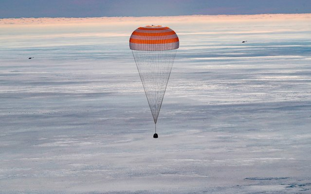 The Soyuz MS-13 capsule carrying the International Space Station (ISS) crew of NASA astronaut Christina Koch, Russian cosmonaut Alexander Skvortsov and Luca Parmitano of the European Space Agency, descends beneath a parachute before landing in a remote area outside the town of Dzhezkazgan (Zhezkazgan), Kazakhstan, on February 6, 2020. (Photo by Sergei Ilnitsky/Pool via AFP Photo)