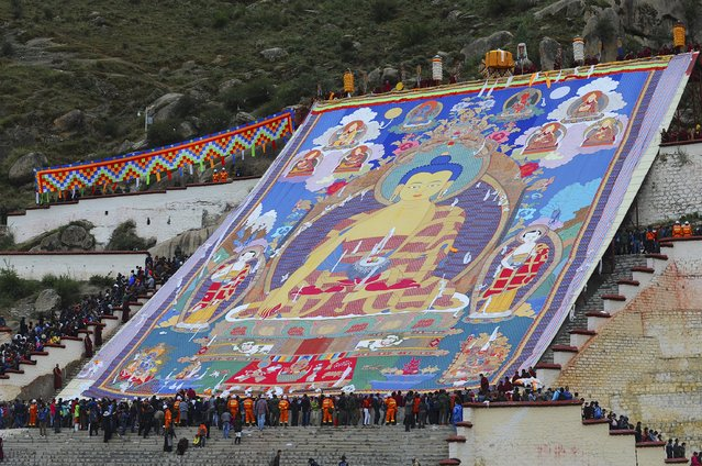 Tibetan Buddhists and tourists view a huge Thangka, a religious silk embroidery or painting displaying a Buddha portrait, during the Shoton Festival at Drepung Monastery in Lhasa, Tibet Autonomous Region, China, August 14, 2015. (Photo by Reuters/China Daily)