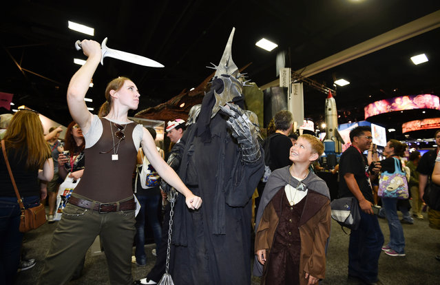 "Fans play around an actor posing in the role of the Witch King of Angmar from the ""Hobbit"" on day 1 of the 2014 Comic-Con International Convention held Thursday, July 24, 2014 in San Diego. (Photo by Denis Poroy/Invision/AP Photo)"