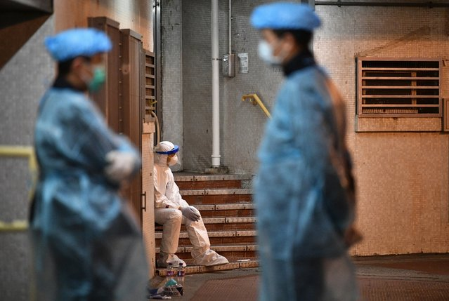 Medical personnel wearing protective suits stay near a block's entrance on the grounds of a residential estate in Hong Kong, early on February 11, 2020, after two people in the block were confirmed to have contracted the new coronavirus, according to local newspaper reports. (Photo by Anthony Wallace/AFP Photo)