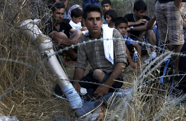 An Afghani refugee has his prosthetic leg removed as he sits behind barbed wire at the Greek-Macedonian border, near the village of Idomeni, August 21, 2015. (Photo by Yannis Behrakis/Reuters)