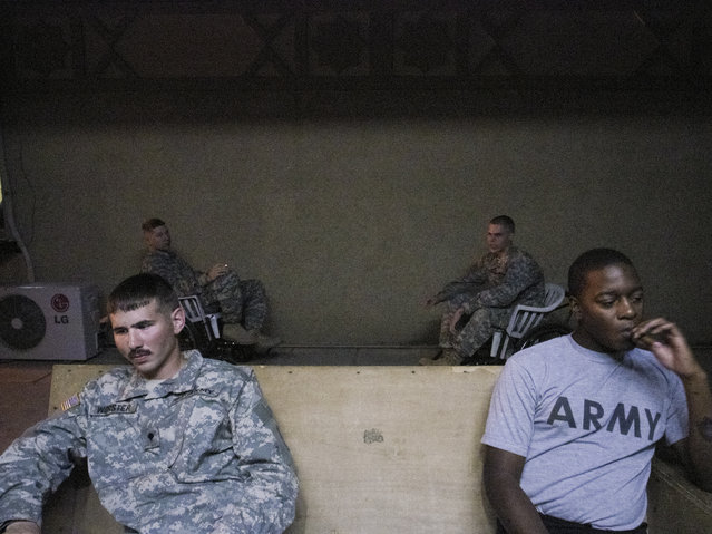 Specialist James Worster (left) and Sergeant Brandon Benjamin take a cigarette break while in the Baghdad ER. Two months after this photo was taken, Worster died of an overdose of a sedative, propofol. Drug abuse was widespread in the hospital unit. (Photo and caption by Van Agtmael/Harrison Jacobs/Magnum Photos)