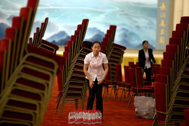 Workers clear the area at the end of the Greece-China Maritime Cooperation to Fuel Growth Bilateral Business Forum held at the Great Hall of the People in Beijing, China, July 4, 2016. (Photo by Ng Han Guan/Reuters)
