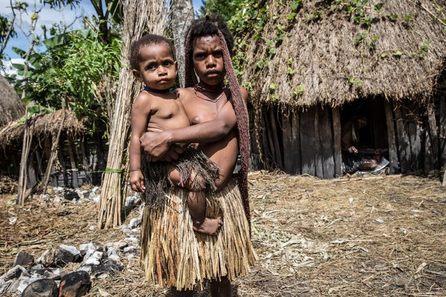 A girl from the Dani tribe holds a baby at Obia Village on August 9, 2014 in Wamena, Papua, Indonesia. (Photo by Agung Parameswara/Getty Images)