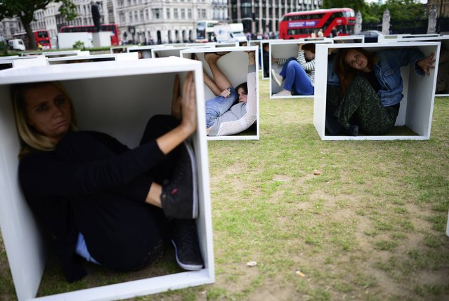 Volunteers sit in wooden boxes at Parliament Square, to represent living conditions in Gaza, during a protest in London August 14, 2014. Some one hundred and fifty men, women and children crammed into boxes in a bid to illustrate the conditions faced by the people of Gaza trapped by the blockade, in an event organised by Oxfam. (Photo by Dylan Martinez/Reuters)