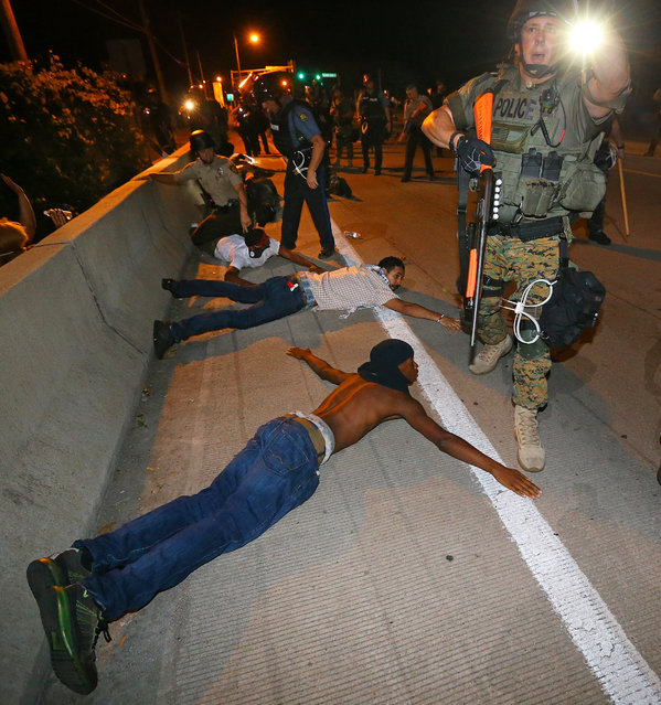 Police begin arresting dozens of protesters on West Florissant Avenue after they refused to leave the area and some began throwing objects at officers in Ferguson, Mo. early Wednesday, August 20, 2014. On Aug. 9, 2014, a white police officer fatally shot Michael Brown, an unarmed black 18-year old, in the St. Louis suburb. (Photo by Curtis Compton/AP Photo/Atlanta Journal-Constitution)