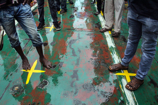 Commuters stand on yellow marks that indicates the physical distancing to curb the COVID-19 coronavirus from spreading on a ferry at Likoni ferry terminal, in Mombasa on March 27, 2020. The Kenyan government put measures at the terminal in place, where thousands of people cross daily, including mandatory use of masks, deployment of armed police officers and reducing number of people boarding a ferry. (Photo by AFP Photo/Stringer)