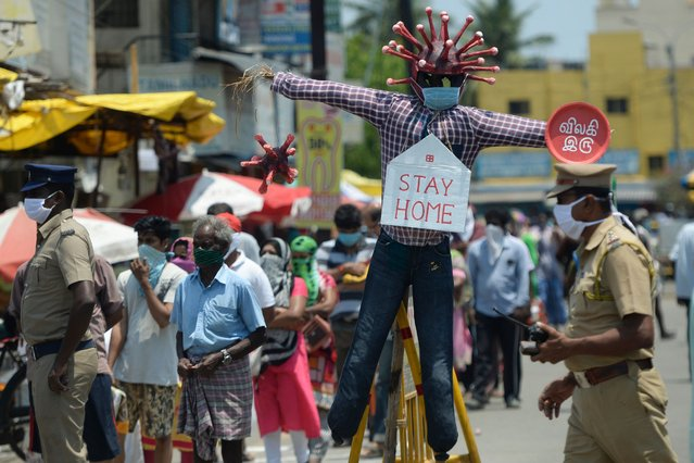 People stand in queue keeping social distance beside a Covid-19 awareness scarecrows placed by Chennai municipality at a market during a government-imposed nationwide lockdown as a preventive measure against the COVID-19 coronavirus, in Chennai on April 11, 2020. (Photo by Arun Sankar/AFP Photo)