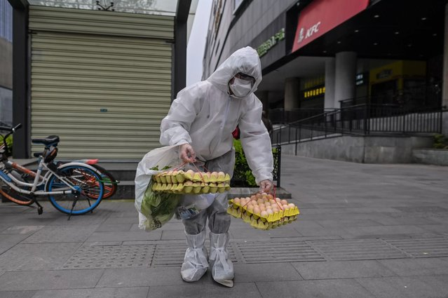 A person wearing a protective suit walks on a street in Wuhan, China's central Hubei province on April 3, 2020. Wuhan, the central Chinese city where the coronavirus first emerged last year, partly reopened on March 28 after more than two months of near total isolation for its population of 11 million. (Photo by Hector Retamal/AFP Photo)