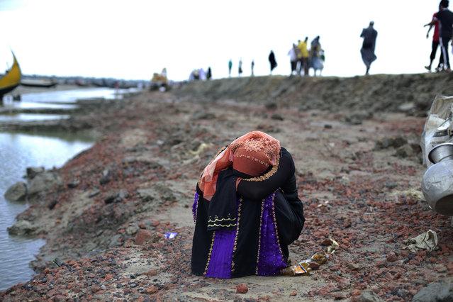 A Rohingya Muslim woman who just crossed the border from Myanmar into Bangladesh puts her head down and cries in Teknaf, Bangladesh, Friday, September 29, 2017. (Photo by Gemunu Amarasinghe/AP Photo)