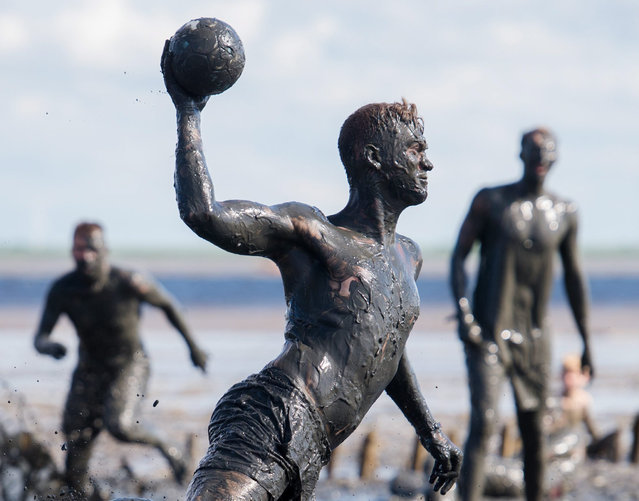 Athletes vie for the ball during the Mud Olympics in Brunsbuettel,Germany, 30 July 2016. Since 2004, amateur athletes have been competing in various events at the mouth of the Elbe river on the North Sea. The proceeds are traditionally donated to the Schleswig-Holstein Cancer Society. (Photo by Daniel Bockwoldt/EPA)