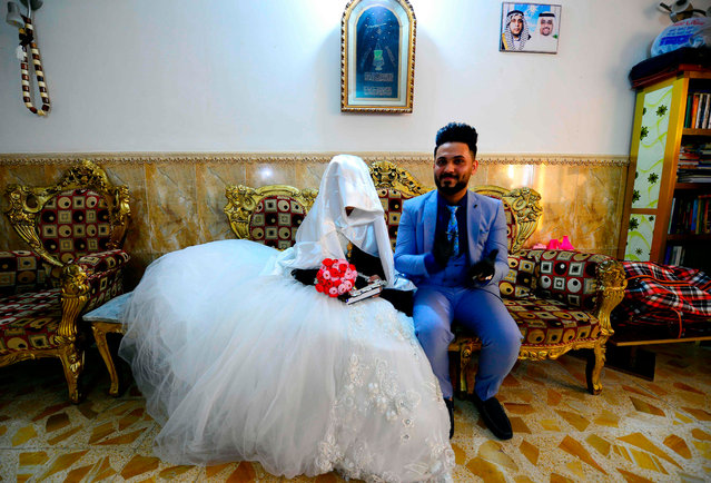 An Iraqi couple prepares to get married as authorities imposed restrictions on large gatherings in a bid to stem the spread of the COVID-19 coronavirus in Iraq's central shrine city of Najaf on April 9, 2020. (Photo by Haidar Hamdani/AFP Photo)