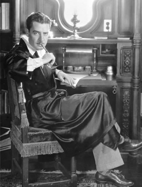 American silent star John Gilbert (1892–1936) sucks thoughtfully on the end of a pen at his writing desk, circa 1930. (Photo by General Photographic Agency)