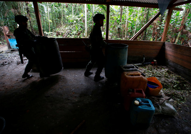 Colombian anti-narcotics policemen lift barrels in a cocaine lab, which, according to the police, belongs to criminal gangs in rural area of Calamar in Guaviare state, Colombia, August 2, 2016. (Photo by John Vizcaino/Reuters)