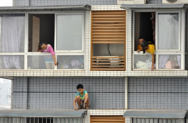 A twelve-year-old boy sits outside a window of his eleventh-floor apartment as his relatives try to ask him to come back back inside, in Yibin, Sichuan province, September 8, 2014. The boy was afraid of being punished by his mother for not finishing his homework on time. After two hours' standoff, he was persuaded by police and family members to come inside. (Photo by Reuters/Stringer)