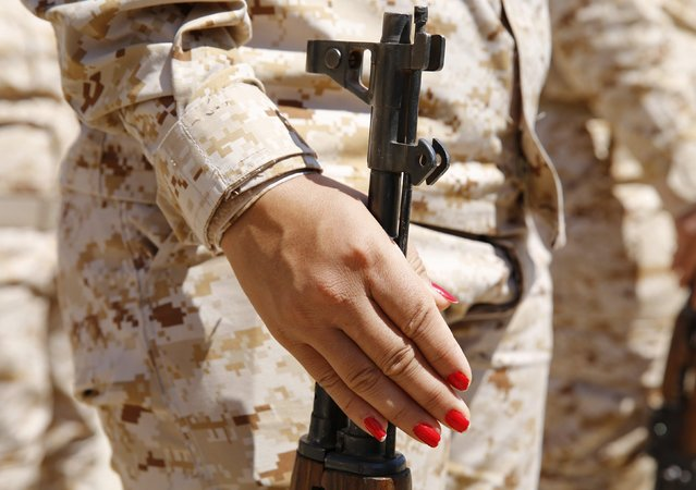 The painted nails of a Kurdish Peshmerga female fighter are seen as she holds her gun during combat skills training before being deployed to fight Islamic State militants, at their military camp in Sulaimaniya, northern Iraq September 18, 2014. (Photo by Ahmed Jadallah/Reuters)