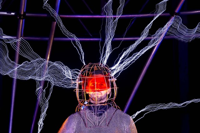 Blaine stands inside the apparatus, surrounded by a million volts of electric currents streamed by tesla coils. The stunt, sponsored by Intel, is the latest of daredevil endeavors by the magician whose previous stunts included being encased in ice for over 60 hours in Times Square, on October 5, 2012. (Photo by John Minchillo/Associated Press)