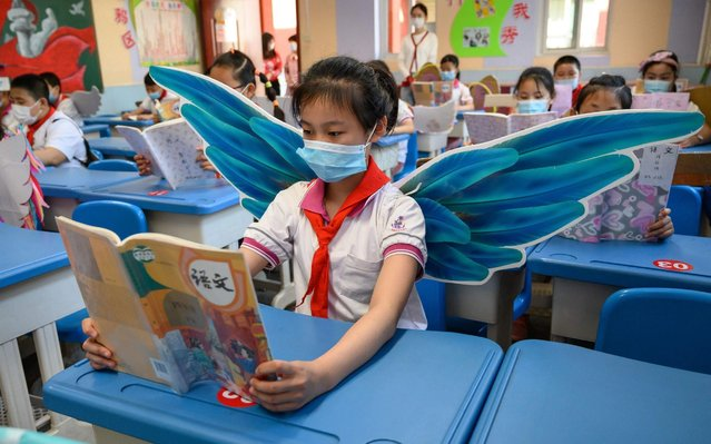 This photo taken on May 20, 2020 shows elementary school students wearing wings to maintain social distancing amid concerns of the COVID-19 coronavirus, in a classroom in Taiyuan in China's northern Shanxi province. (Photo by AFP Photo/China Stringer Network)