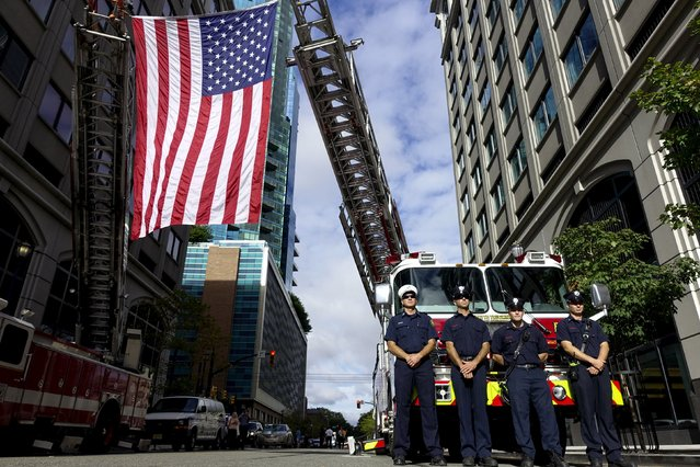 Jersey City Fire Department members attend a ceremony for 9/11 victims at a memorial across from New York's Lower Manhattan and One World Trade Center in Exchange Place, New Jersey September 11, 2015. (Photo by Eduardo Munoz/Reuters)