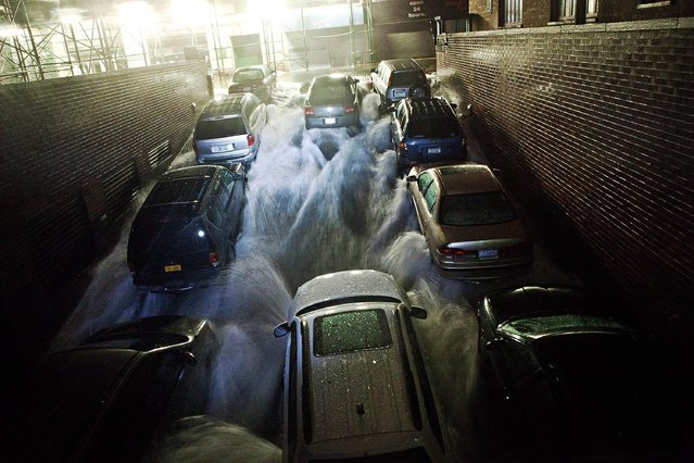 Rising water, caused by Hurricane Sandy, rushes into a subterranian parking garage on October 29, 2012, in the Financial District of New York, United States. Hurricane Sandy, which threatens 50 million people in the eastern third of the U.S., is expected to bring days of rain, high winds and possibly heavy snow. New York Governor Andrew Cuomo announced the closure of all New York City will bus, subway and commuter rail service as of Sunday evening. (Photo by Andrew Burton/AFP Photo)