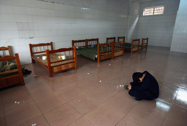 A boy sits in his dormitory after he was attacked by another boy with a scoop at an assistance center February 24, 2005 in Shenzhen, Guangdong Province, China. (Photo by Cancan Chu/Getty Images)