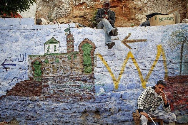 Men sit on a painted wall behind Bab el Bahr gates of Rabat's Medina September 21, 2014. (Photo by Damir Sagolj/Reuters)