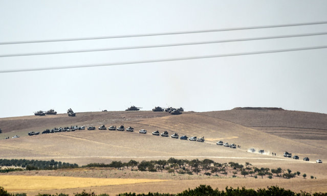 This picture taken from the Turkish Syrian border city of Karkamis in the southern region of Gaziantep, on August 24, 2016 shows Turkish army tanks and pro-Ankara Syrian opposition fighters moving two kilometres west from the Syrian Turkish border town of Jarabulus. Turkey's army backed by international coalition air strikes launched an operation involving fighter jets and elite ground troops to drive Islamic State jihadists out of a key Syrian border town. Turkey's state-run Anadolu news agency reported that pro-Ankara Free Syrian Army (FSA) rebels had already penetrated three kilometres (two miles) inside Syria towards the IS-held town of Jarabulus. The air and ground operation, the most ambitious launched by Turkey in the Syria conflict, is aimed at clearing jihadists from the town of Jarabulus, which lies directly opposite the Turkish town of Karkamis. (Photo by Bulent Kilic/AFP Photo)