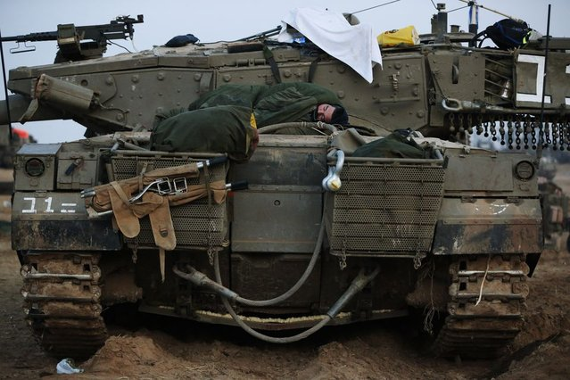 An Israeli soldier sleeps on a tank at a staging area near the Israel Gaza Strip Border, southern Israel, early Tuesday, November 20, 2012. (Photo by Lefteris Pitarakis/AP Photo)