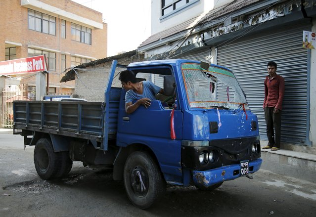 A driver reverses his vehicle after the windshield was broken by an opposition supporter (not pictured), who threw a stone at him for not taking part in a protest against the proposed constitution, during a nationwide strike called by the opposition parties in Kathmandu, Nepal September 20, 2015. (Photo by Navesh Chitrakar/Reuters)