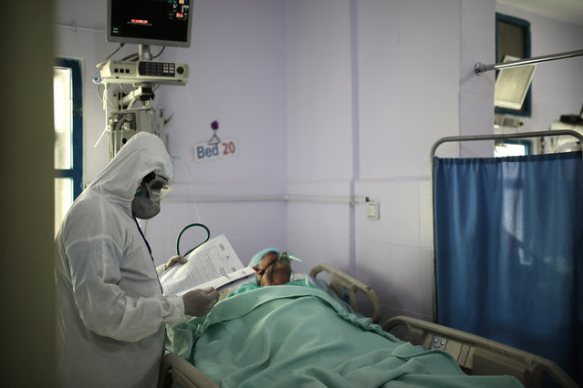 A medical worker wearing personal protective equipment takes care of a COVID-19 patient in an intensive care unit at a hospital in Sanaa, Yemen, Sunday, June 14, 2020. (Photo by Hani Mohammed/AP Photo)