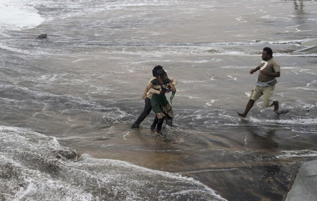 A man, right, rushes to help as another rescues a woman who fell due to strong tidal waves on the Bay of Bengal coast at Gopalpur, Orissa, about 285 kilometers (178 miles) north east of Visakhapatnam, India, Sunday, October 12, 2014. (Photo by Biswaranjan Rout/AP Photo)