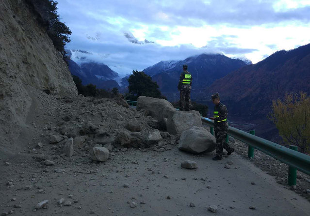 In this photo released by China's Xinhua News Agency, rescuers look at a road blocked by fallen rocks in Paizhen town in Mainling county of Nyingchi city in southwestern China's Tibet Autonomous Region, Saturday, November 18, 2017. A strong earthquake has shaken China's Tibet region. The U.S. Geological Survey says the 6.3 magnitude quake hit at a depth of about 6 miles (10 kilometers) about 36 miles (58 kilometers) northeast of Nyingchi. (Photo by Liu Pengchao/Xinhua via AP Photo)