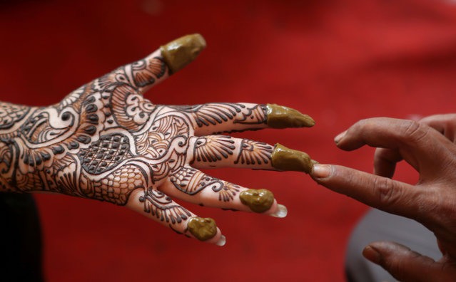 An Indian woman show her hand decorated with henna design ahead of Diwali, the Festival of Lights, in Callcutta India, October 17, 2014. During Diwali, the entire house is cleaned and new clothes are purchased for the whole family. This is followed by lighting oil lamps around the house and setting off firecrackers. (Photo by Piyal Adhikary/EPA)
