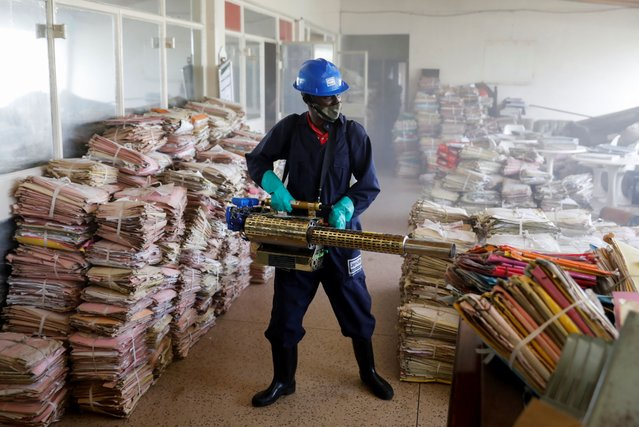 A sanitation worker fumigates using sodium hypochlorite in an archive room to fight the spread of the coronavirus disease (COVID-19) in the Milimani commercial courts in Nairobi, Kenya, July 17, 2020. (Photo by Baz Ratner/Reuters)