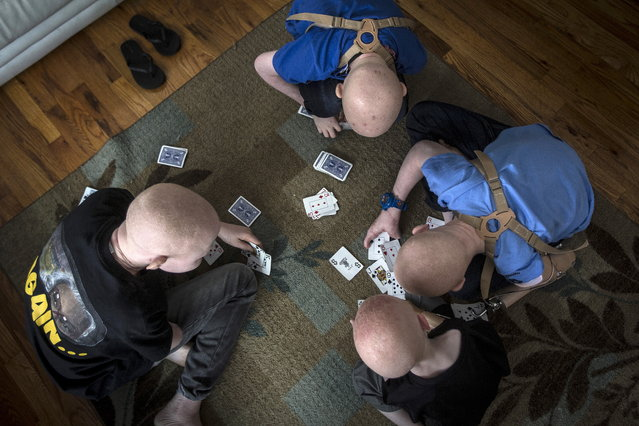 Children from Tanzania play cards in the living room in Staten Island. (Photo by Carlo Allegri/Reuters)