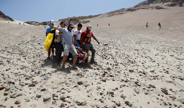 Medics, helped by fans, evacuate Leonardo Martinez of Bolivia, who was injured after crashing with his quad during the 3nd stage of the 2013 Dakar Rally. (Photo by Victor R. Caivano/Associated Press)