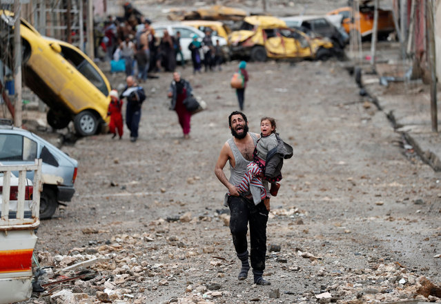 A man cries as he carries his daughter while walking from an Islamic State-controlled part of Mosul towards Iraqi special forces soldiers during a battle in Mosul, Iraq March 4, 2017. (Photo by Goran Tomasevic/Reuters)