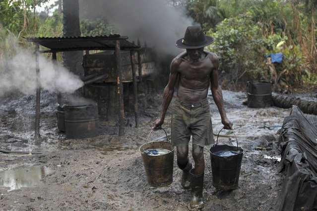 Ebiowei, 48, carries refined oil in buckets at an illegal oil refinery site near river Nun in Nigeria's oil state of Bayelsa November 27, 2012. Thousands of people in Nigeria engage in a practice known locally as 'oil bunkering' - hacking into pipelines to steal crude then refining it or selling it abroad. (Photo by Akintunde Akinleye/Reuters)