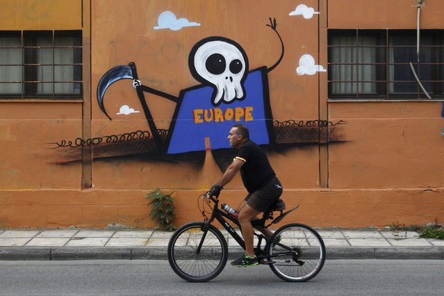 A man rides his bike past a graffiti depicting Europe as a Grim Reaper with a small door on his body, standing in front of a barbed wire fence and waving, in the northern city of Thessaloniki, Greece, September 29, 2015. (Photo by Alexandros Avramidis/Reuters)