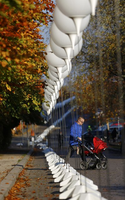"""A man walks past stands with balloons placed along the former Berlin Wall location at Mauerpark, which will be used in the installation """"Lichtgrenze"""" (Border of Light) in Berlin November 7, 2014. (Photo by Pawel Kopczynski/Reuters)"""