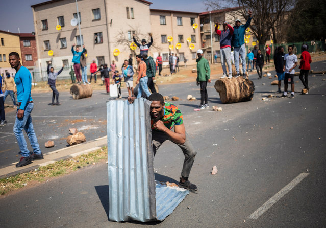 Protesters prepare to attack police during clashes between the local community members and police forces, after it was alleged by the community that an unarmed teenager was shot and killed by the police, in Johannesburg, South Africa, 27 August 2020. Local residents of Eldorado Park community clashe with police forces after attacking the local police station alleging that they killed a 16 year old teenager, after he left his house to find food. (Photo by Kim Ludbrook/EPA/EFE)