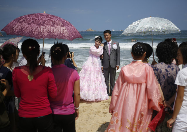 A newlywed couple pose, during a photo shoot on Sijung Ho beach in North Korea, Tuesday, August 18, 2015. The couple gathered with their friends and family members to have their pictures taken after their wedding ceremony. (Photo by Dita Alangkara/AP Photo)