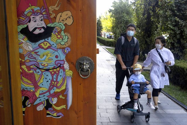 Residents wearing masks to curb the spread of the coronavirus walk on a Beijing street on Monday, August 24, China has gone several days without reporting a new local case of COVID-19, with the Beijing International Film Festival among public events that are returning. (Photo by Ng Han Guan/AP Photo)
